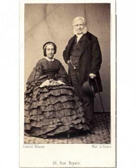 Couple âgé: femme en macarons assise, homme à favoris debout