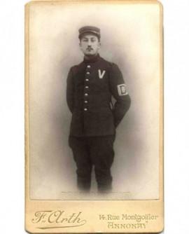 Homme à moustache en uniforme (brassard avec D, un V sur la poitrine)