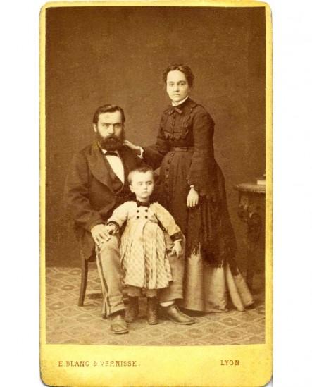 Couple avec enfant: homme barbu assis, femme debout