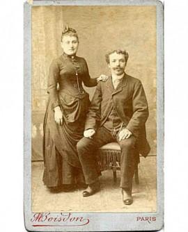 Couple: homme moustachu assis, femem debout appuyée sur lui