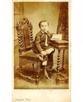 Jeune garçon assis, le pied gauche ramené sur le genou droit