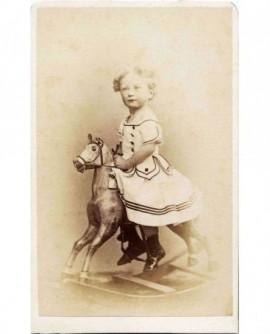 Garçon bouclé en robe sur un cheval à bascule