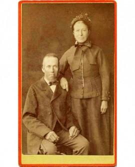 couple (homme assis, la femme en chapeau, debout, s'appuyant sur lui)