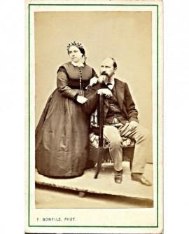 Couple: homme barbu assis et femme en bonnet debout