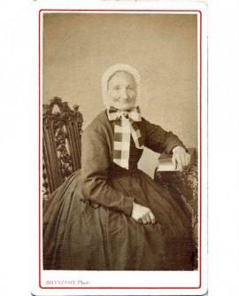 Femme âgée en bonnet assise, un livre sous la main