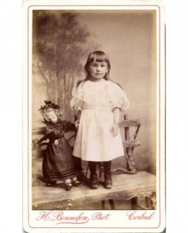 Fillette en robe blanche avec une poupée en porcelaine