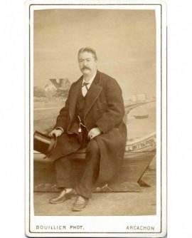 """Homme moustachu assis devant le canot """"l'Intrépide"""""""