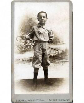 Jeune garçon posant avec une canne