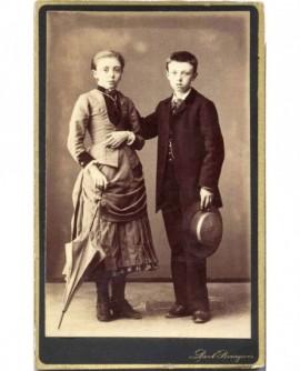Homme, chapeau à la main, fille tenant une ombrelle