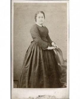 Femme en pied appuyée à un fauteuil