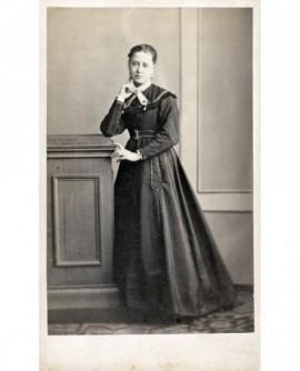 Jeune femme appuyée sur un bahut