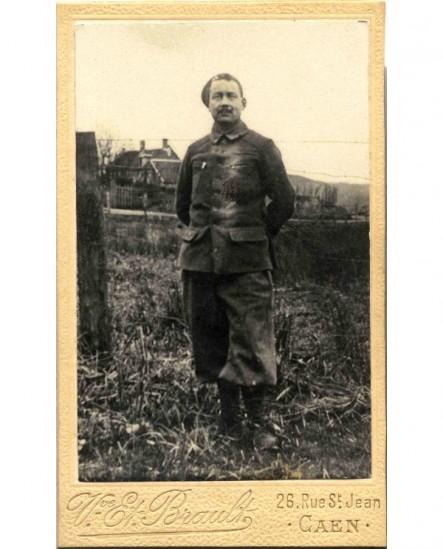 Militaire en chechia debout dans un jardin rural