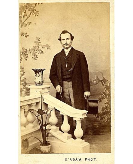 Homme moustachu sur un perron, chapeau et canne à la main