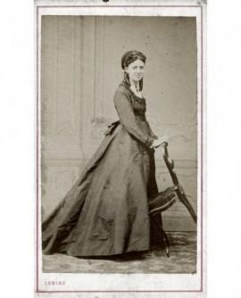 Jeune femme debout tenant une chaise inclinée