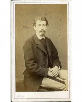 Homme à mouche et moustache assis