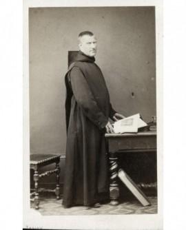 Moine bénédictin tenant un livre ouvert (sur une photo de cloître)