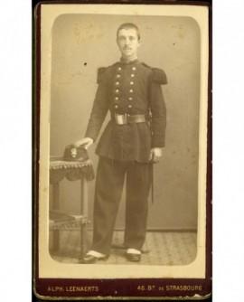 Militaire debout, tête nue, la main sur son képi