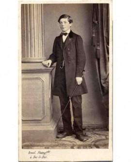 Jeune garçon posant avec une canne, accoudée à une colonne