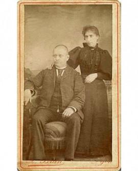 Couple: homme chauve assis, femem debout s'appuyant sur son épaule