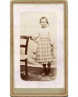 Fillette debout en jupe et corsage, appuyée à une chaise