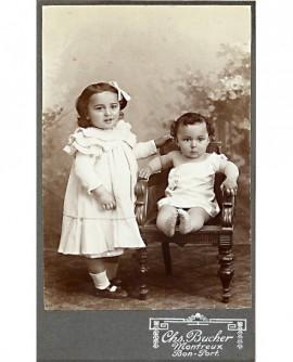 Grande soeur en robe et petit frère bébé en chemise, épaule dénudée