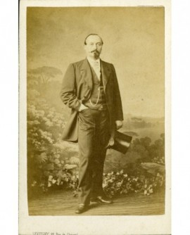 Homme à mouche et moustache debout, son chapeau à la main