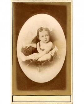 Bébé en chemise, épaule dénudée, assis sur coussin