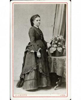 Femme debout en robe à tournure, main sur un livre