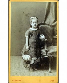 Petite fille debout tenant un tonneau de cantinière