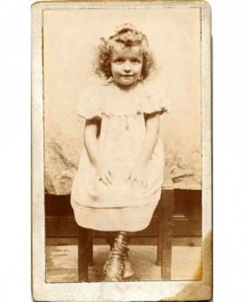 Portrait de fillette en robe, assise sur un banc, mains sur les genoux