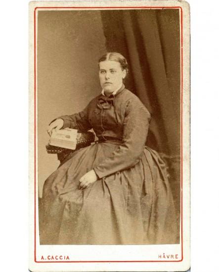 Femme assise tenant un album-photo