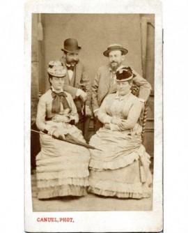 Femmes en chapeau assises, hommes barbus en melon debout