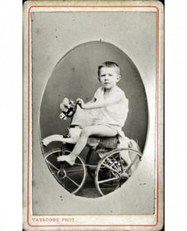Enfant en chemise sur cheval tricycle (jouet)