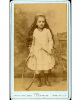 Petite fille aux longs cheveux avec baguette et cerceau (jouet)