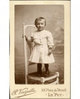 Enfant souriant debout sur une chaise