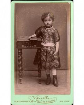 Petite fille en pied, accoudée à une table