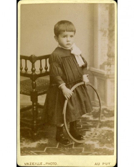Jeune garçon en sarrau tenant un cerceau (jouet)