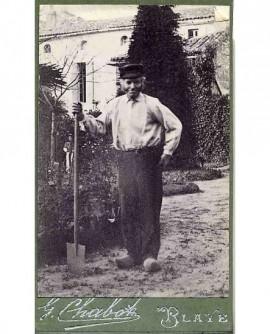 Jardinier en sabot et casquette, tenant une pelle