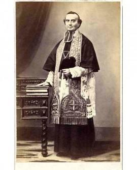 Ecclésiastique en camail et étole debout, sa barrette à la main