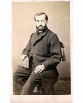 Homme barbu assis, un livre sur les genoux