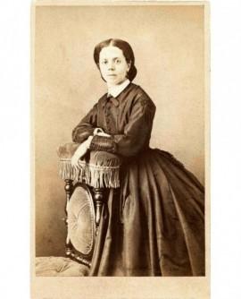 Jeune femme en robe, accoudée à une chaise