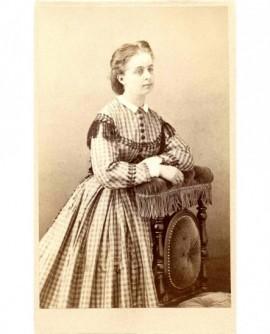 Jeune femme en robe Vichy, accoudée à une chaise