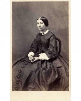 Femme en robe assise tenant un éventail