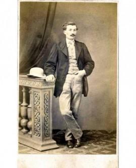 Homme moustachu debout, son melon posé sur la balustrade