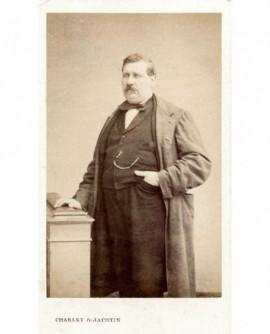 Homme moustachu debout, la main sur des livres