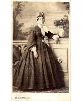 Femme en robe et capote debout, accoudée à une balustrade