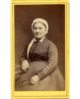 Femme en coiffe assise, accoudée sur des livres