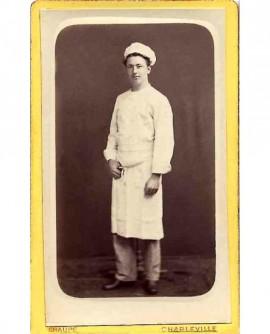 Homme debout en tenue de travail (cuisinier/pâtissier?)