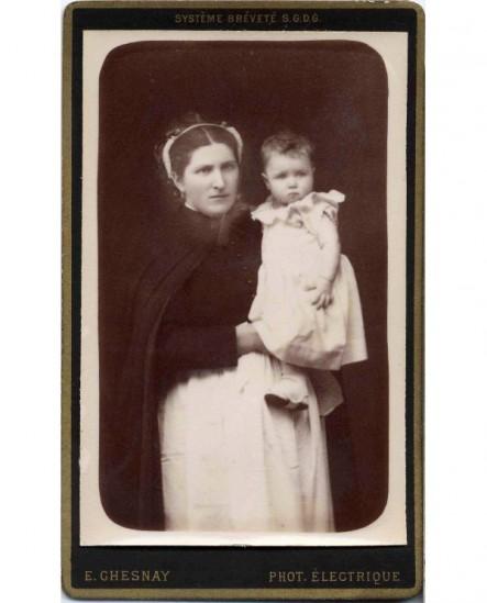 Nourrice en coiffe et tablier blanc présentant un bébé