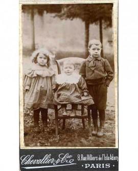 Fratrie de 3 enfants en extérieur (bébé, assis au centre)